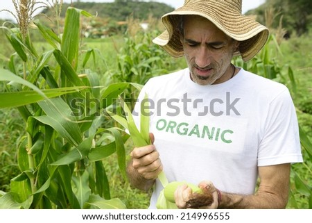 Organic farming: portrait of an eco farmer showing corn beside the field - stock photo