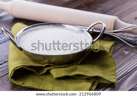 Organic flour in  bowl on brown table. Selective focus, horizontal.
