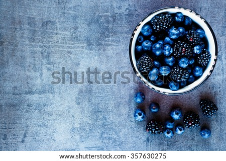 Organic fresh dark berries in vintage mug over rustic background with space for text, top view. Agriculture, Gardening, Harvest Concept. - stock photo