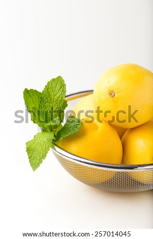 organic, fresh mint leaves and lemons in a metal strainer over a white background with copy space, close up, vertical - stock photo