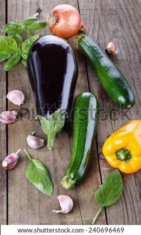 Organic fresh zucchini, eggplant, yellow capsicum, brown onion, garlic and basil over rustic wooden background - stock photo