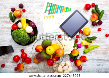 Organic fruit and vegetable on the table with a tablet PC.  - stock photo