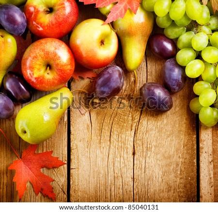 Organic Fruits over wood background. Autumn harvest - stock photo