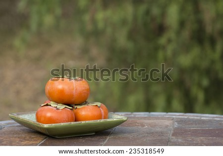 Organic Fuyu persimmons on a green plate on outdoor table - stock photo