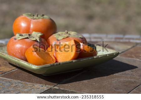 Organic Fuyu persimmons on a green plate on outdoor table