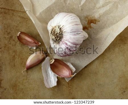 Organic garlic on an old rustic stone chopping board - stock photo