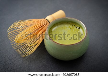 Organic Green Matcha Tea in a small cup over slate background - stock photo