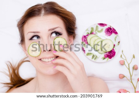 organic green natural spa treatment: beautiful blond young lady having fun applying slices of cucumber to her skin face happy smiling & looking up at copy space on white background closeup portrait - stock photo