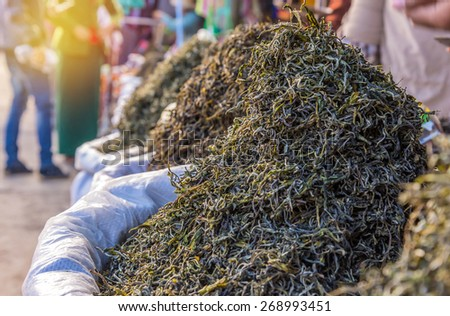organic green tea dry process after picked in market. - stock photo