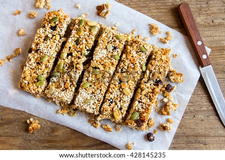 Organic homemade granola bars on rustic wooden background - Healthy vegetarian snack - stock photo
