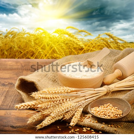 Organic ingredients for bread preparation with golden sunrise on background - stock photo