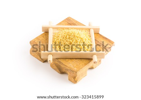 organic millet seeds in a ceramic bowl on wooden rustic table - stock photo