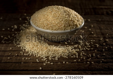 Organic natural sesame seeds against wooden background - stock photo