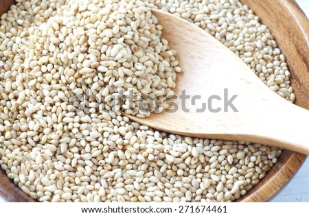 Organic natural sesame seeds on white wood table - stock photo