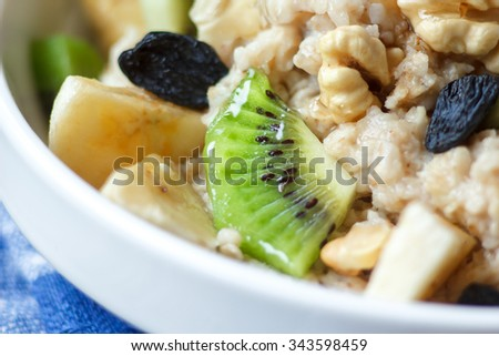 Organic oatmeal porridge in white ceramic bowl with bananas, honey, walnuts, kiwi fruit and raisins. Healthy breakfast - health and diet concept on the napkin, close up. - stock photo
