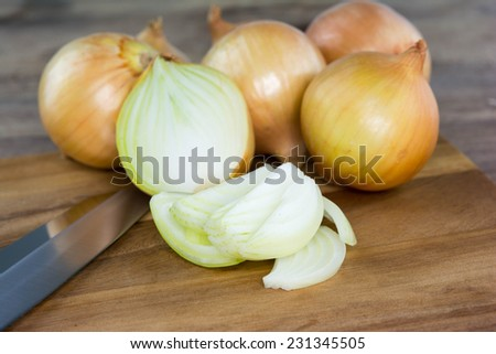 Organic onion on board on wooden background. Selective focus, horizontal.  - stock photo