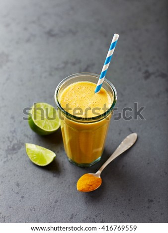 Organic orange and carrot smoothie with turmeric powder - stock photo