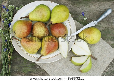 Organic pears on plate with flowers and knife