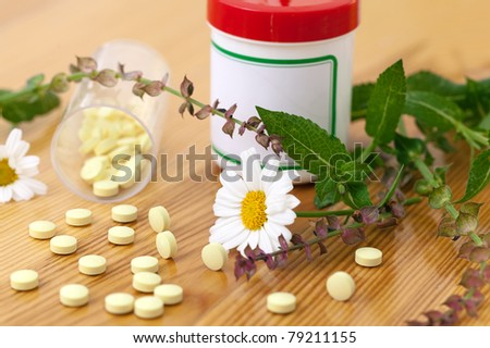 Organic pills and bottles with Medicinal plants, Focus on the pills in the foreground - stock photo