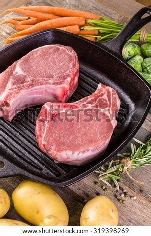 Organic pork lion chops of thick cut on cast iron frying pan.