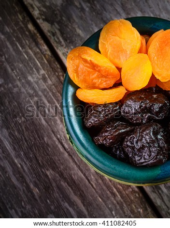Organic prunes, dried plums and dried apricots in old tableware on rustic table. Top view - stock photo
