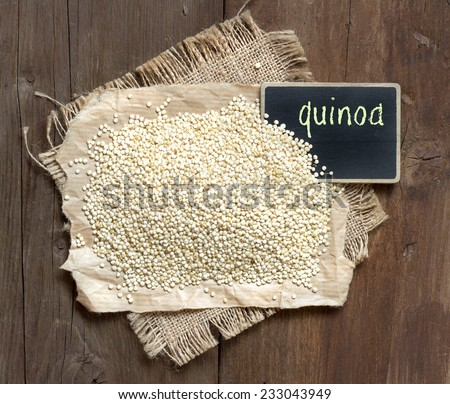 Organic quinoa with a small chalkboard on a wooden table - stock photo