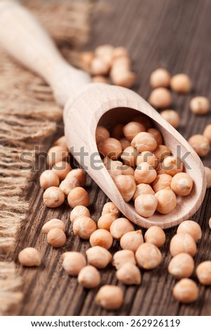 Organic raw chick peas healthy protein nutrition super food in wooden spoon on vintage background - stock photo