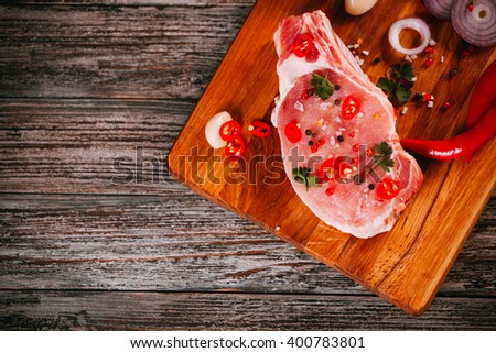 Organic raw pork meat on chopping board. Decoreted with spices, fresh garlic, chili and parsleys. fresh food prepared for cooking. Set of products for grill, barbecue.  top view, space for text - stock photo