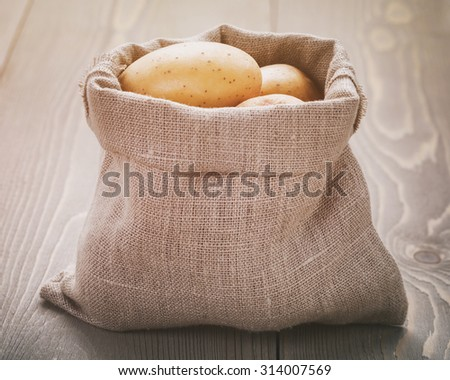 organic raw potato in sack bag on wood table, vintage toned - stock photo
