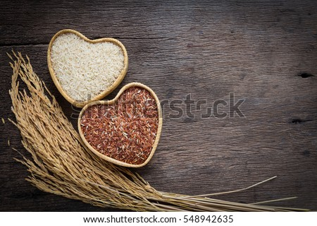 Organic rice grain,brown rice in heart shape bamboo basket over wooden background