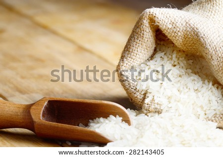 Organic rice grains in burlap sack with copy-space - stock photo