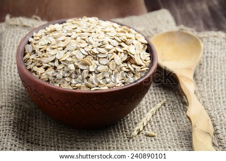 Organic rolled oats in brown bowl on linen bag, close up - stock photo