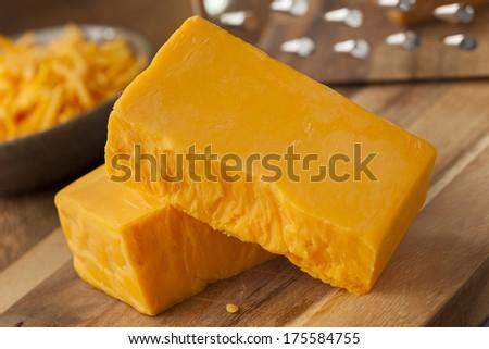 Organic Sharp Cheddar Cheese on a Cutting Board - stock photo