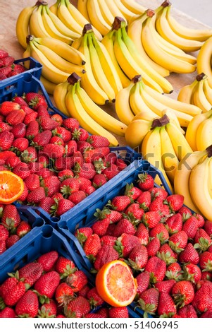 Organic strawberries and bananas  lined up for sale at a market