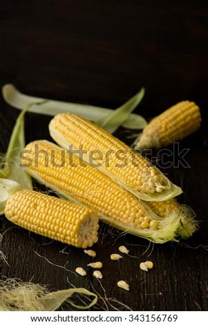 Organic sweet corn on wooden table. Selective focus. - stock photo