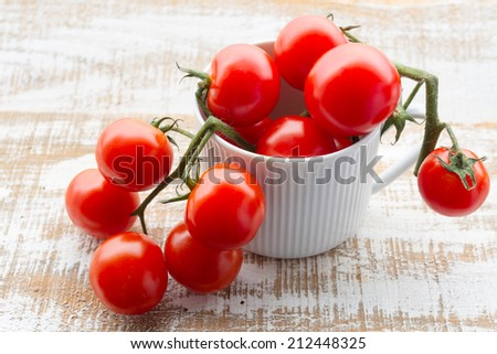 Organic tomatoes on white wooden floor