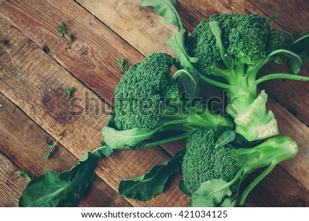 Organic vegetables on wood. Fresh broccoli on wooden table. Toned image - stock photo