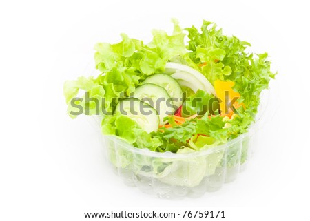 Organic vegetables salad in plastic bowl on white background - stock photo
