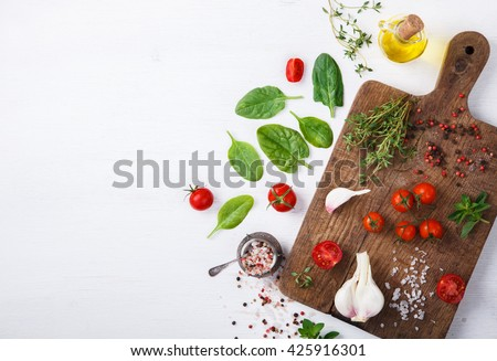 Organic vegetarian ingredients, olive oil and seasoning on rustic wooden cutting board over dark vintage background with space for text.Healthy food, or diet nutrition concept.Fresh Vegetables