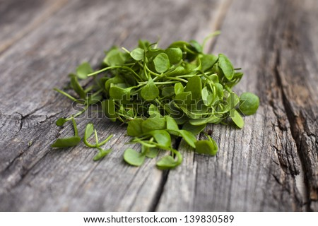 Organic watercress leaves on a rustic wooden board - stock photo