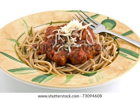 Organic whole wheat spaghetti with tomato basil sauce and meatballs in colorful dish isolated on white background - stock photo