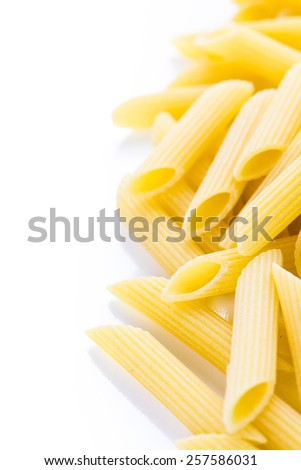 Organic yellow rigate pasta on a white background.