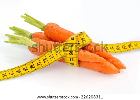 organically grown carrots with tape measure. fresh fruit and vegetables are always healthy. symbol photo for healthy diet. - stock photo