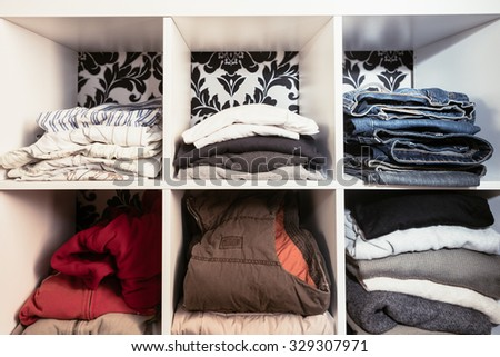 organised wardrobe, folding and stacking clothes vertically - stock photo