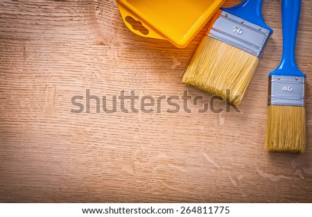 organized copyspace aerial view two paintbrushes with blue handles and yellow paint can on wooden board construction concept  - stock photo