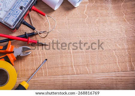 organized copyspace electrical tools multimeter tester nippers screwdriver roll insulating tape On Wooden Board  - stock photo