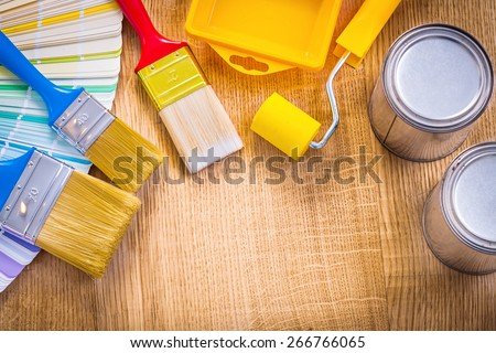 organized copyspace painting tools color palette paint brush roller tray can on wooden board  - stock photo