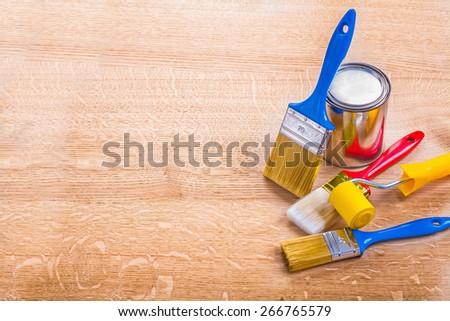organized copyspace set of paint brushes roller and can on wooden board  - stock photo