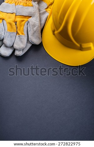 organized copyspace yellow helmet and protective gloves on black background  - stock photo