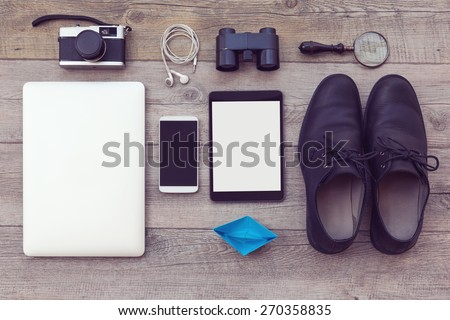 Organized modern and retro objects on wooden table. Adventure essentials for man - stock photo